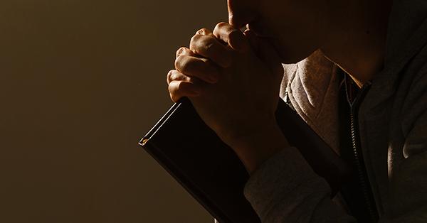 Homem com um livro na mão rezando